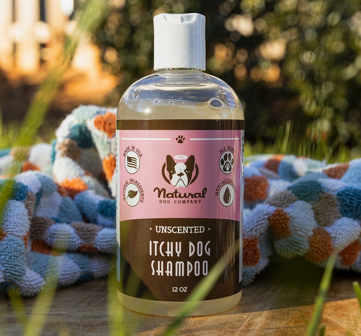 Bottle of all-natural shampoo for itchy dogs, outside next to a towel.